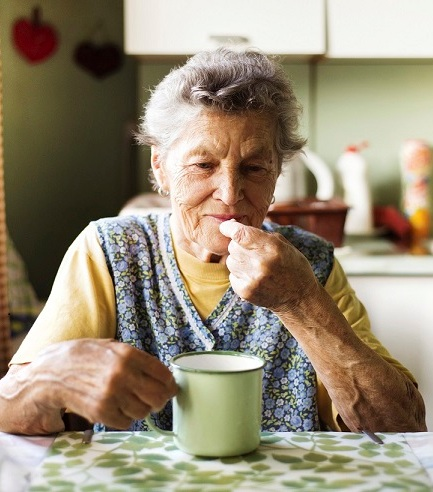 OlderWoman_eating_in_kitchen-cropped