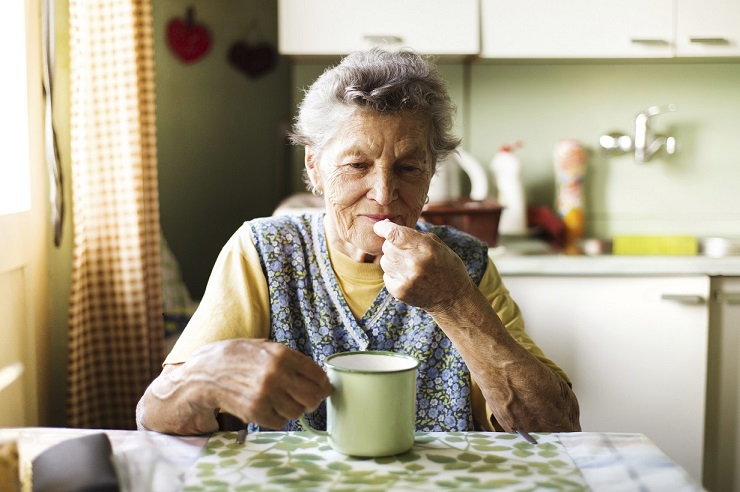 Older Woman eating in kitchen